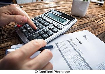 Person's Hand Calculating Invoice