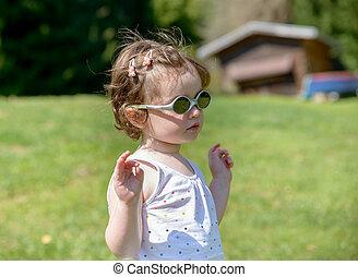 a, petite fille, dans jardin, à, lunettes soleil