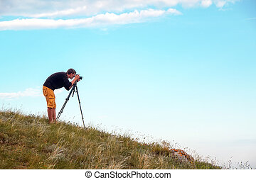 A photographer with a tripod and camera makes photos of landscapes on the mountain. Man in work.