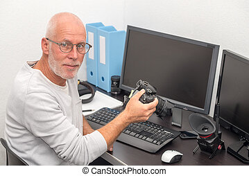 photographer with camera at office with computer