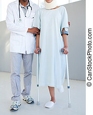 A physical therapist helping a patient with neck brace and on crutches in a hospital