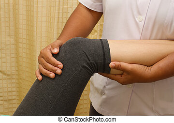 a physio therapist trying to test the knee and leg