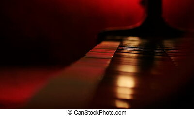 A pianist closes a lid to the piano, red background