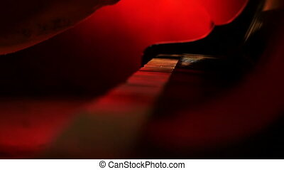 A pianist opens a lid to the piano and begins to play a red yellow background