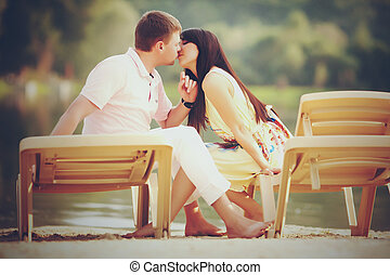 A picture in warm tones of young couple sitting on the beach beds