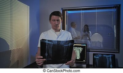 A picture of a male doctor. The doctor stands in the tomography room and studies the x-ray picture. Professional people at work.