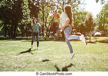 A picture of girl who has caughted frisbee with her hand. She made a jump to catch it. Her mom is very happy about that.