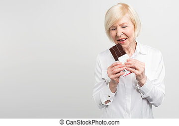 A picture of mautre lady eading a bar of milk chocolate. She...