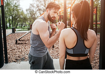 A picture of young man and woman exercising ouside in park. He is showing how to do boxing in a right way. She is looking at it.