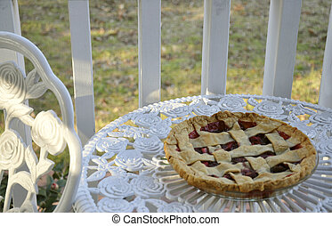A pie cooling in the warm afternoon sun on a white metal...