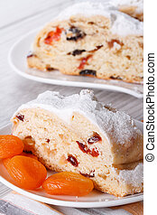 A piece of cake with raisins, dried apricots closeup. vertical