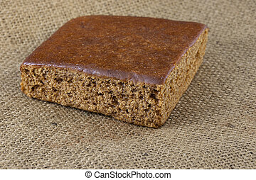 a piece of gingerbread cake on burlap canvas