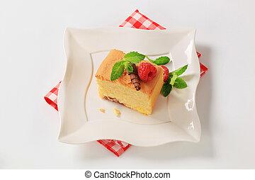 sponge cake - a piece of homemade sponge cake on white plate