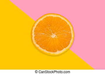 A piece of orange on a pink and yellow background. View from above