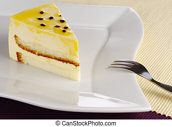 A piece of passionfruit cake on white plate with cake fork (Selective Focus)