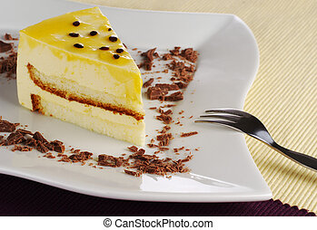 A piece of passionfruit cake with chocolate shavings on white plate with fork (Selective Focus)