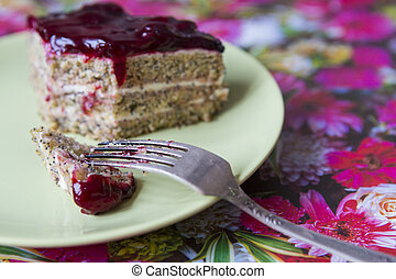 A piece of poppy cherry cake on a plate.