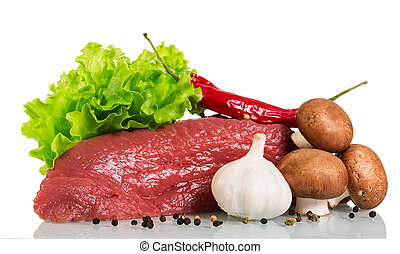 A piece of raw beef, mushrooms, lettuce, garlic and black pepper isolated on white.