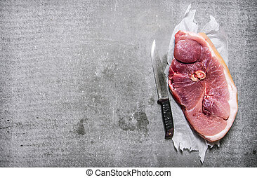 A piece of raw fresh meat with a chopping knife.