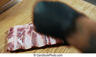 A piece of raw meat falls on the wooden table.