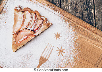 A piece of sliced apple pie with cinnamon on vintage wooden background texture. Top view.