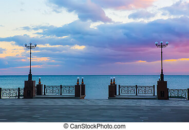 a pier by the sea with beautiful street lights