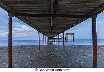 A pier going out to sea at sunset