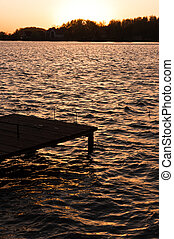 A pier on the shore with sunset