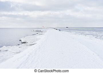 A pier to the lighthouse at the mouth in winter