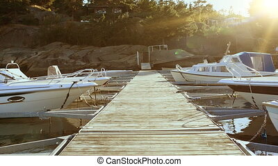 A pier with private boats laid up at Scandinavian stony...