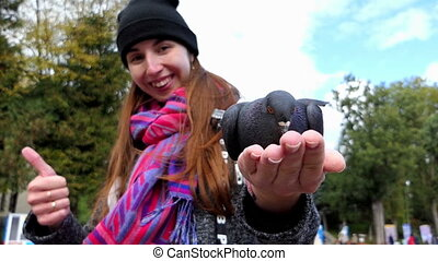 A pigeon is fed from the palm of a smiling woman in slo-mo