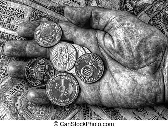 A pile of anniversary coins in a human's hand over a background of banknotes in black and white
