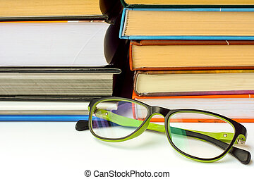 A pile of books with eyeglasses