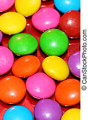 A pile of chocolate candies with a colorful outer shell