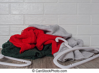 A pile of clothes against a white brick wall. Scattered clothes hangers. Fashion, style. Sweaters in red, green and melange colors. Mess, home routine, storage. Wardrobe, hygge and knitwear.