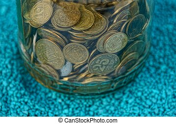 a pile of coins in a glass jar on blue sand