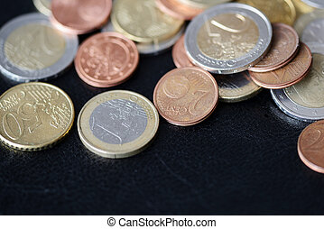A pile of euro coins scattered on a dark surface close up