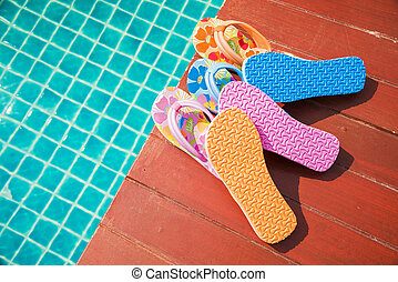 a pile of flip-flops at the swimming pool