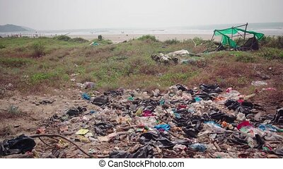 A pile of garbage lies near the sea shore. The concept of environmental pollution.