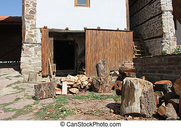 A pile of logs in front of the barn