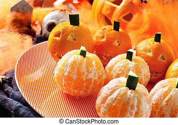 a pile of mandarines ornamented as Halloween pumpkins with scary ornaments in the background, such as skulls, spiders and spider web
