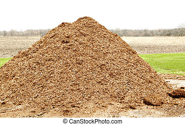 pile of natural mulch - a pile of natural mulch on farm land