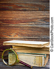 a pile of old books and magnifier on wooden background. the concept of the research, the study. with space for text
