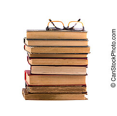 A pile of old books isolated on white background. Glasses from above.