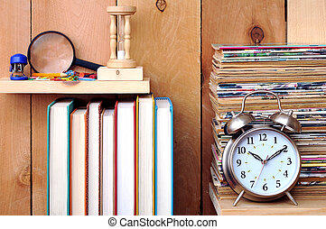 a pile of old magazine, clock, books and stationery