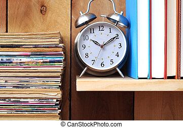 old magazine, clock, books on wooden shelf