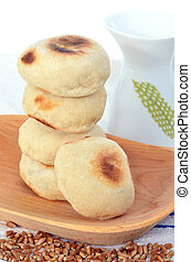 A pile of pita bread on a wood plate