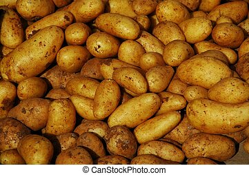 a pile of potatoes at a market stand