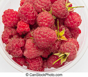 a pile of red fresh raspberries located on a white background