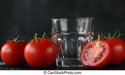 A pile of red ripe tomatoes with green leaves and dense tomato juice being poured into glass.